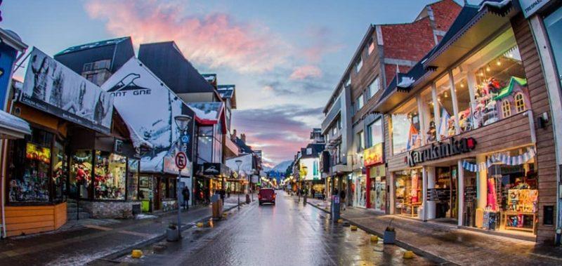 Ushuaia - Avenida San Martin com o chão molhado e comercio dos dois lados da avenida. Céu Azul com nuvens vermelhas.