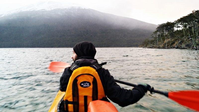 Turista passeando de Caiaque na laguna e ao fundo montanha coberta com o pico de neve