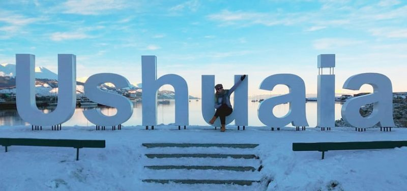 Inverno em Ushuaia - Placa escrito Ushuaia na cor branca com uma turista em frente a placa fazendo pose para foto