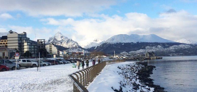 Ushuia no Inverso - Orla de Ushuaia com pessoas passeando, carros parados e prédios atrás, ao fundo montanhas cobertas de neve e céu azul com nuvens brancas.