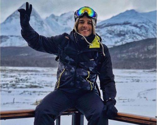 Fábio Beltrão em uma jornada pelo Ushuaia. Em segundo plano, o chão e as montanhas cobertas de neve completam a fotografia.