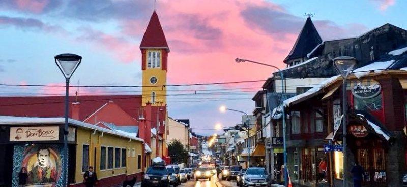 Ushuaia - Avenida San Martin com veículos parados dos dois lados da rua em sentido único, e comércios, hotéis, igreja dos dois lados da rua. Céu azul com nuvens avermelhadas.