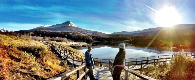 Ushuaia Verão - Casal em cima da passarela olhando um para o outro. Ao fundo uma lagoa e atras do rio montanhas. Céu azul com algumas nuvens na cor roxa e o Sol saindo por trás das montanhas.