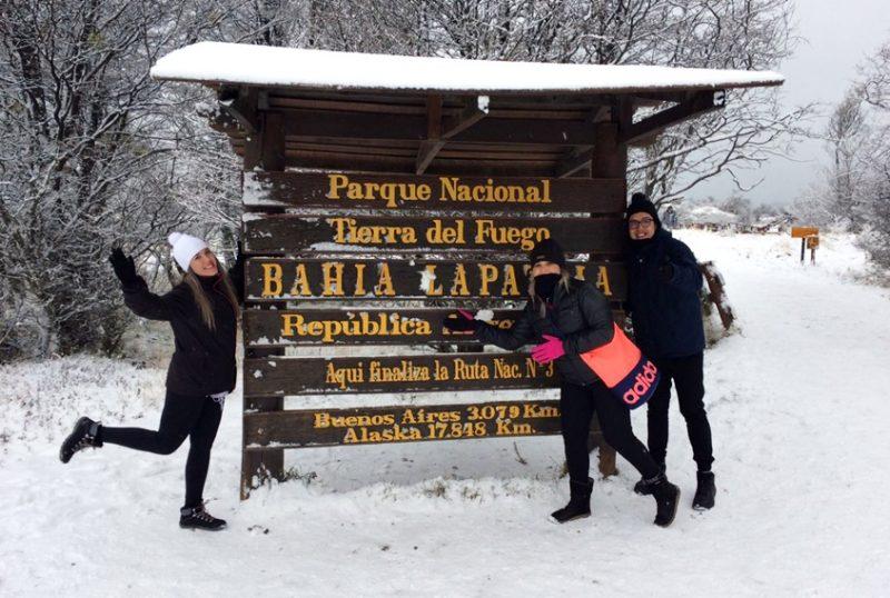 Placa indicando o final da Rota 3 com três turistas fazendo pose para foto. Ao fundo arvores secas com neve nos galhos e no chão