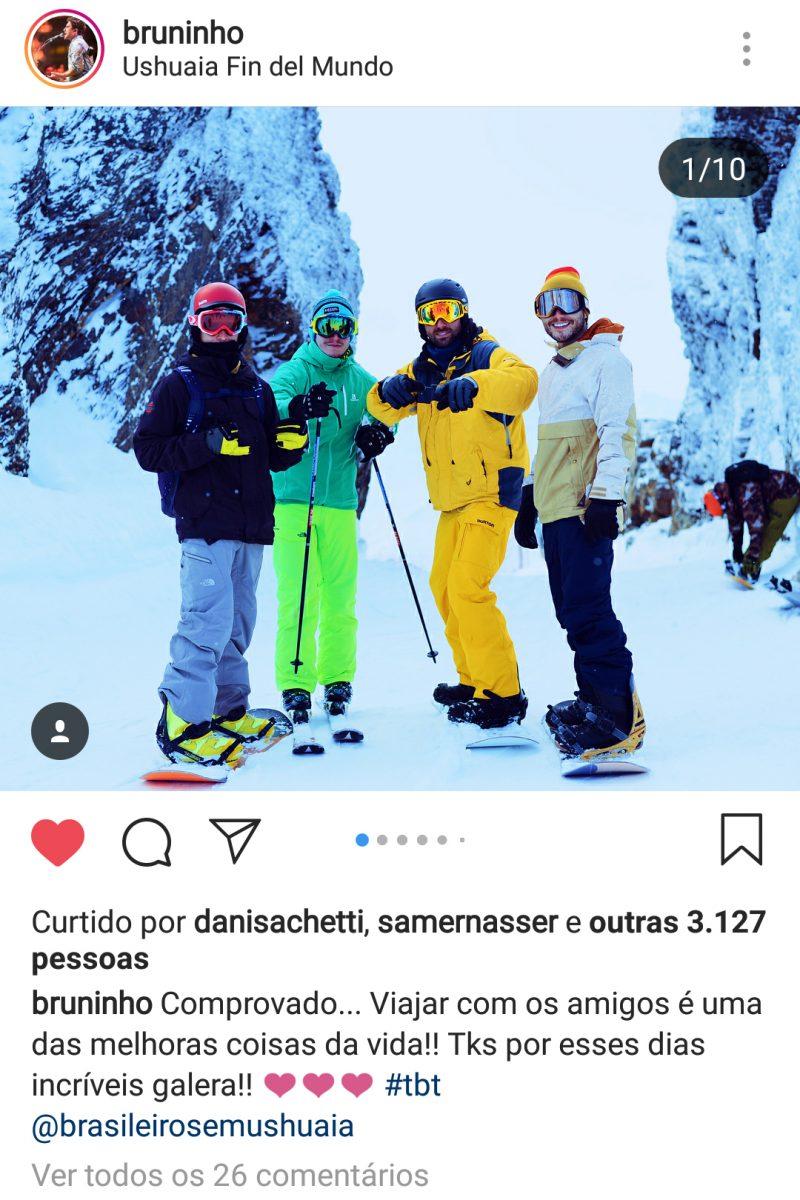 Viagem para Ushuaia - Quatro turistas ao centro da foto com roupas de esqui e equipamento de esqui. No chão muita neve e ao fundo duas montanhas cobertas de neve.