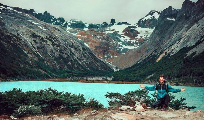 Verão em Ushuaia - Turista agachado ao lado direito da imagem, ao fundo uma lagoa com água azul e montanhas com pouco nave no pico.