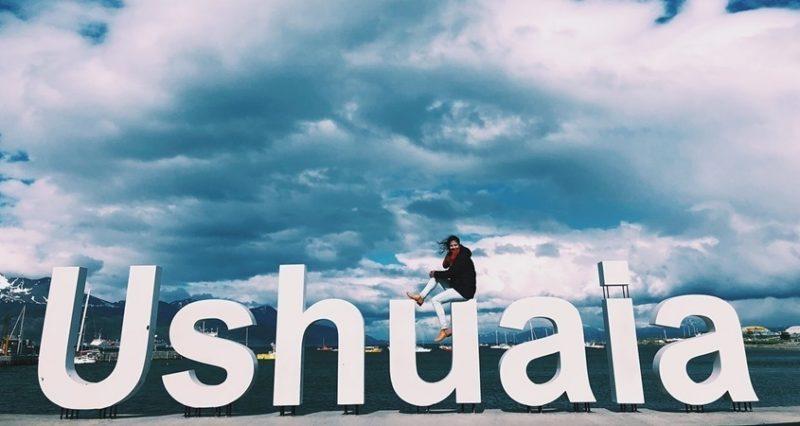 Mulher sentada na Placa de Ushuaia em cima da letra U