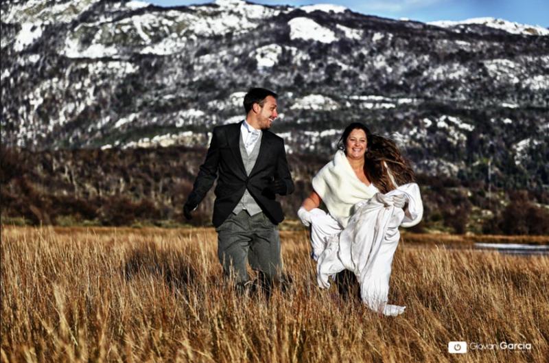 Noivos correndo felizes pelo campo com a mata seca e ao fundo montanhas com neve em Ushuaia