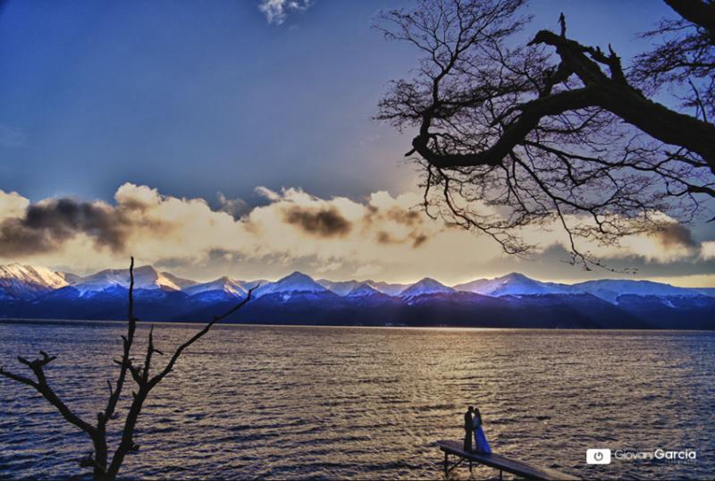 Noivos em um pier na Laguna em Ushuaia, céu azul com poucas nuvens e montanhas com os picos cobertos por neve.
