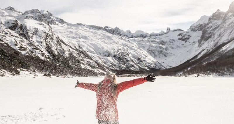 Mulher na neve com os braços abertos e ao fundo montanhas cobertas por neve em Ushuaia
